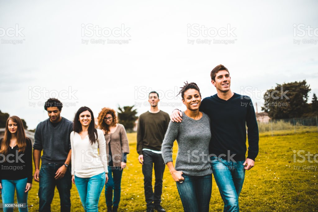 friends walking together in a park stock photo