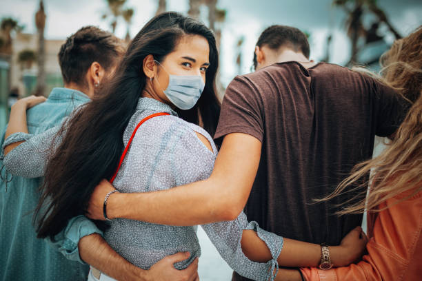 friends walking together wearing the face mask stock photo