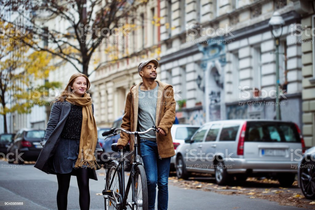 Friends walking with cycle on street during winter royalty-free stock photo