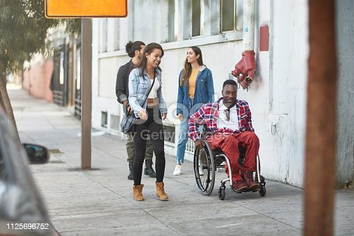 Happy friends walking with disabled man on sidewalk. Multi-ethnic people are spending time together in city. They are wearing casuals during their outing.
