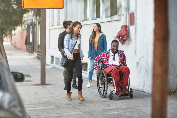 Friends walking with disabled man on sidewalk stock photo