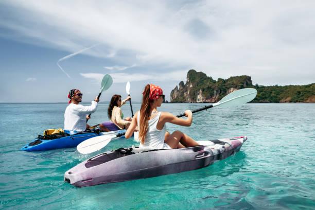 Friends walks by sea kayaks or canoes