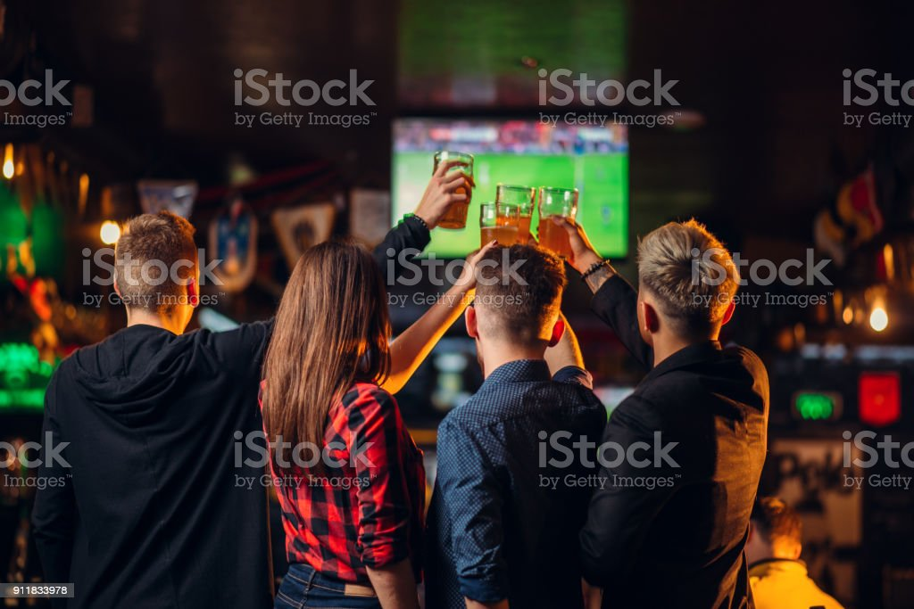 Friends watches football on TV in a sport bar stock photo