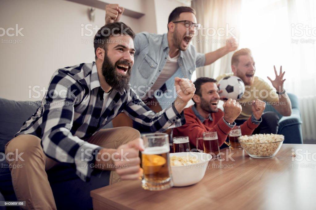 Friends watching a football match on TV stock photo