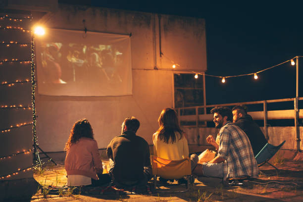 Friends watching a movie on a building rooftop terrace Group of young friends watching a movie on a building rooftop terrace, eating popcorn, drinking beer and having fun watching stock pictures, royalty-free photos & images