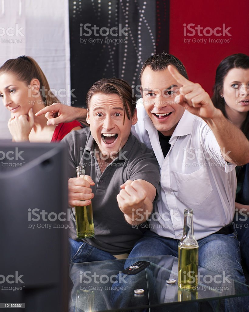 Friends watching an exciting game at TV royalty-free stock photo