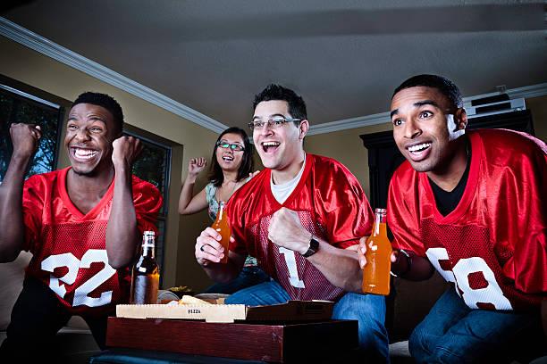 freunde beobachten fußballspiel auf fernseher - rot bekümmerte möbel stock-fotos und bilder