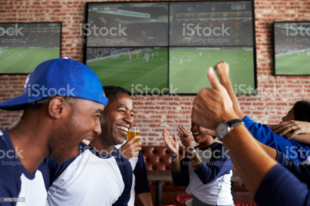 Friends Watching Game In Sports Bar On Screens Celebrating stock photo