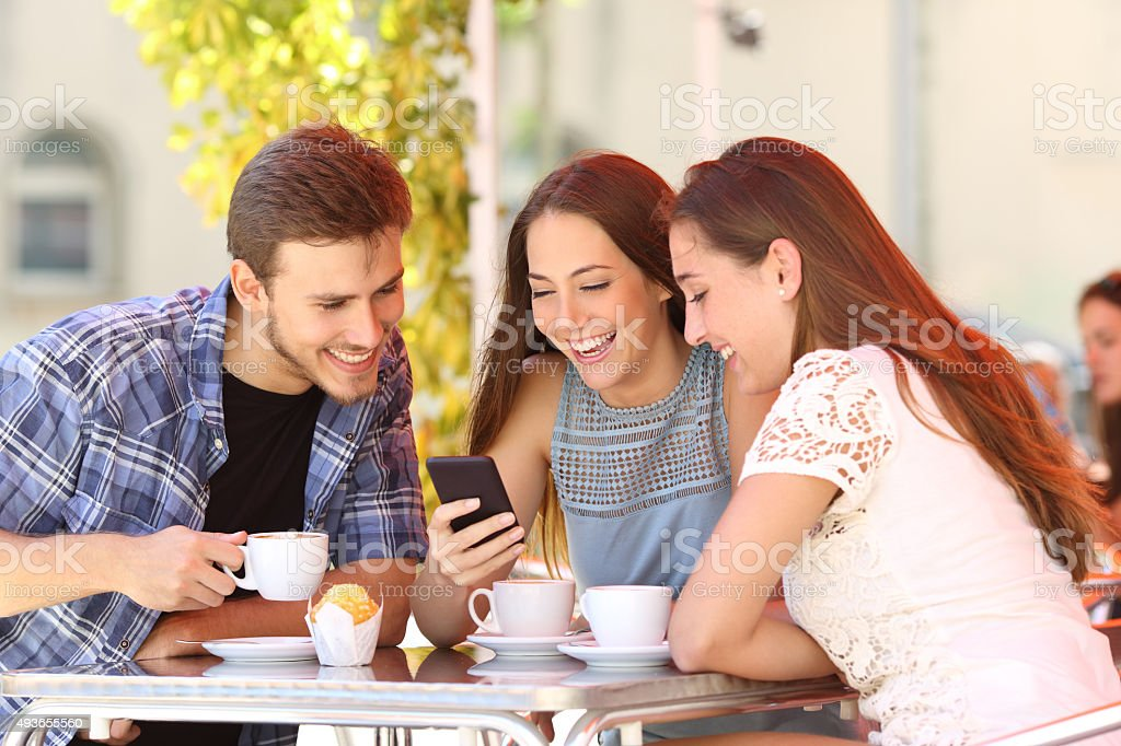 Friends watching media in smart phone in a coffee shop stock photo