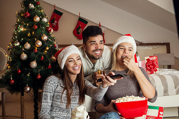 friends watching movie and having fun at christmas eve. - christmas movie foto e immagini stock