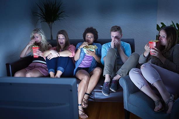 amigos assistir tv show em um pouco assustador de halloween - tv e familia e ecrã imagens e fotografias de stock