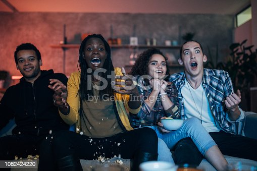 Group of multi ethnic people, friends sitting at home, having fun together, watching a movie.