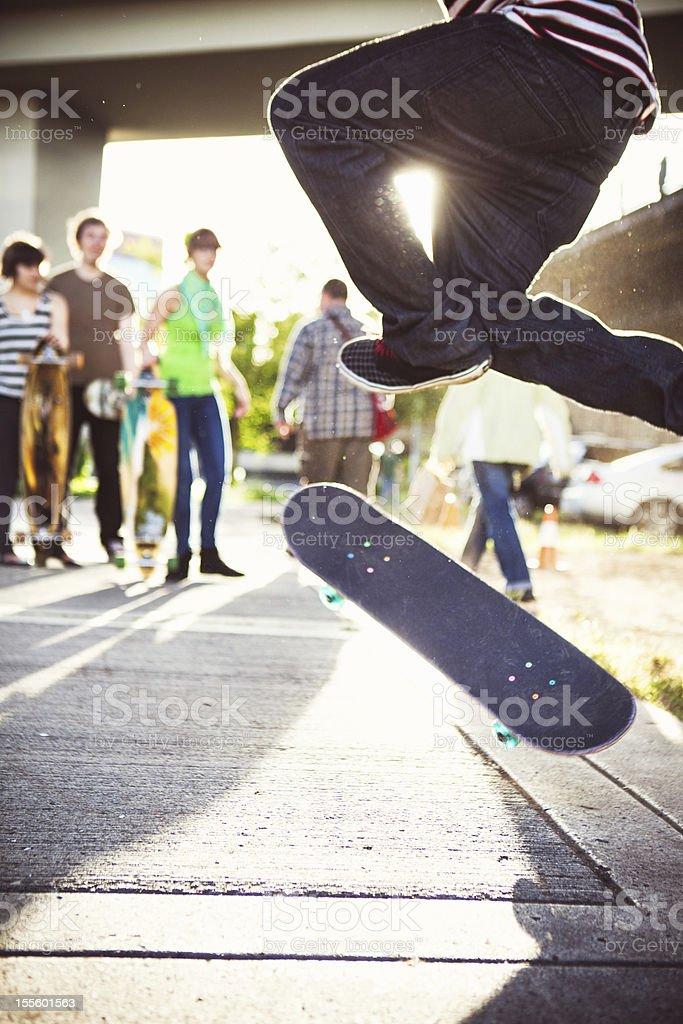 Friends Watching Skateboard Tricks stock photo