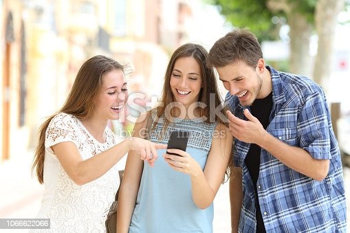 istock Friends watching smartphone content in the street 1066622066
