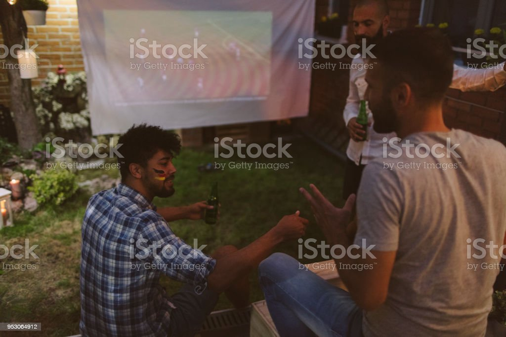 Friends Watching Soccer Game On Big Screen In Backyard stock photo
