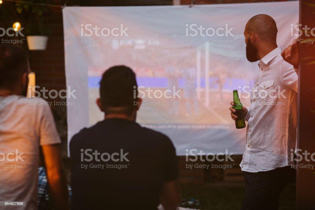 Amis, regarder match de football sur grand écran dans l'arrière-cour - Photo
