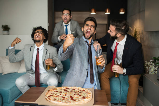 Friends watching sport on tv. Close up of a group of friend having fun man cave couch stock pictures, royalty-free photos & images