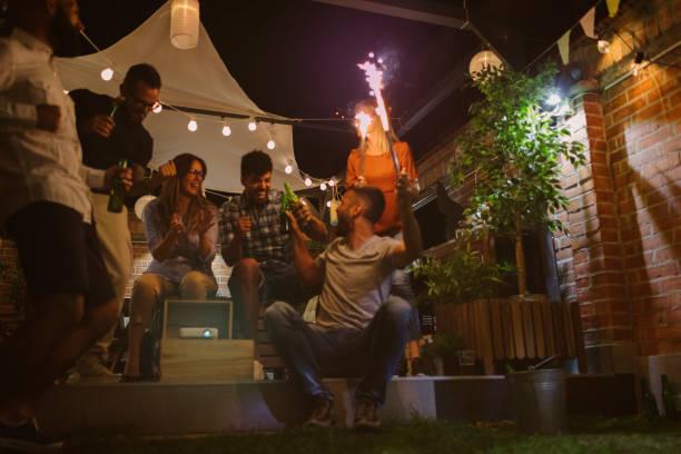 freunde, sportübertragungen auf großbildschirm im hinterhof - terrassen lichterketten stock-fotos und bilder