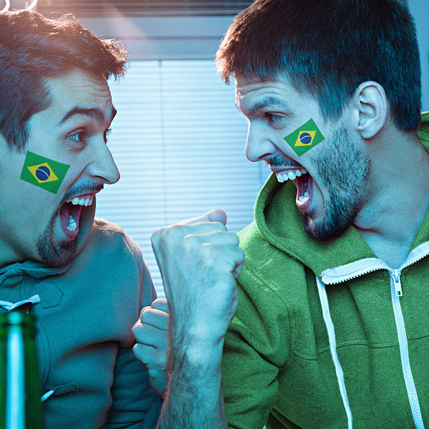 Friends watching sports on TV stock photo