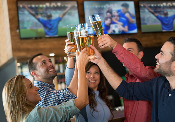 Friends watching the game and making a toast stock photo