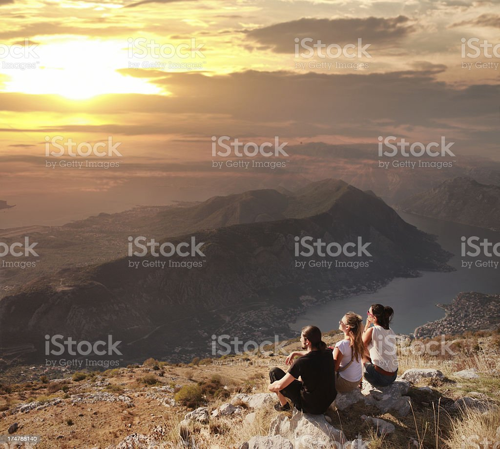 Friends watching the sunset on mountain top royalty-free stock photo