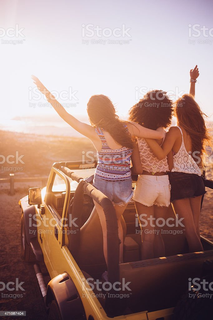 Friends Watching The Sunset Together On A Beach Road Trip Royalty Free Stock Photo