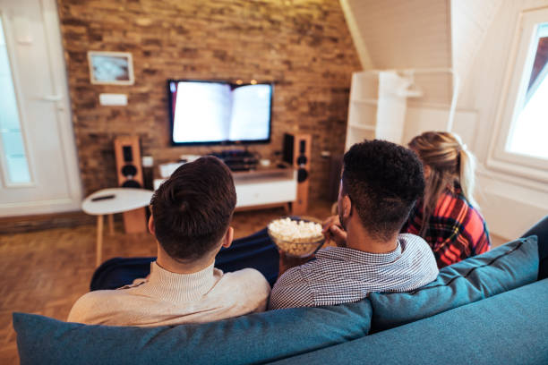 Freunde schauen fernsehen und essen Popcorn, Rückansicht. – Foto