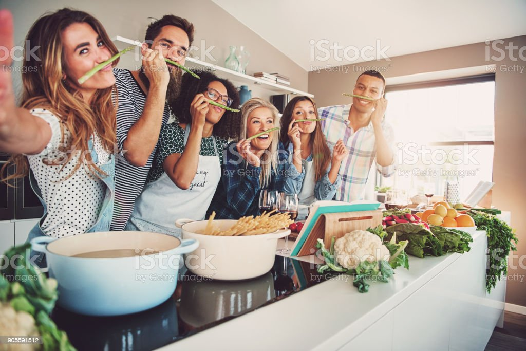 Friends wearing asparagus stalks under their noses stock photo