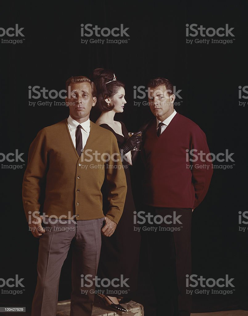 Friends wearing jumper standing together against black background stock photo