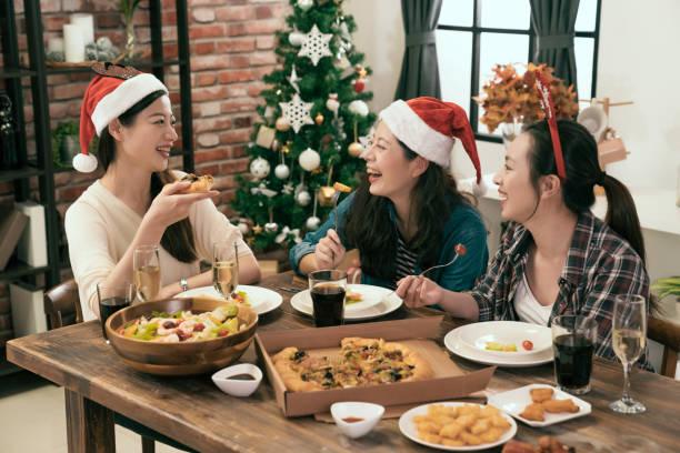 freunde santa hüte tragen und pizza teilen - weihnachten japan stock-fotos und bilder