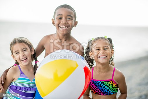 A multi-ethnic group of elementary age children are outside standing together holding a beach ball at the beach. They are smiling and looking at the camera.