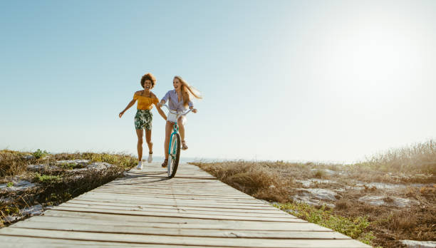 Friends with a bicycle on the seaside boardwalk Two women friends with a bicycle on the seaside boardwalk. Woman riding the bike with her friends holding from the back and running. boardwalk stock pictures, royalty-free photos & images