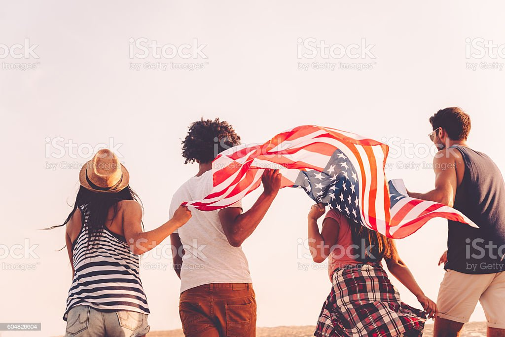 Friends with American flag. Rear view of four young people carrying american flag while running outdoors Activity Stock Photo