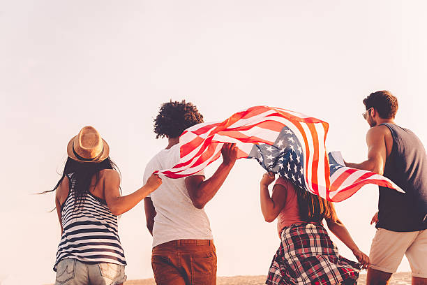Friends with American flag. Rear view of four young people carrying american flag while running outdoors independence day photos stock pictures, royalty-free photos & images