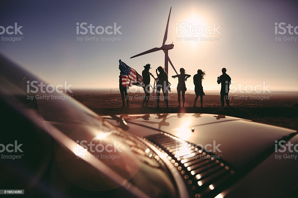 Friends with American flag visiting wind farm on road trip stock photo