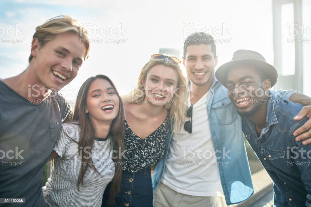 Friends with arms around standing in city stock photo