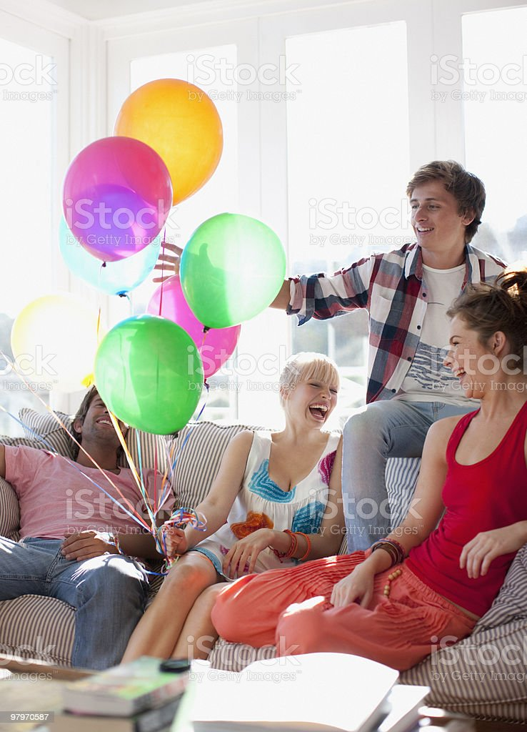 Friends with balloons sitting on sofa in living room royalty-free stock photo