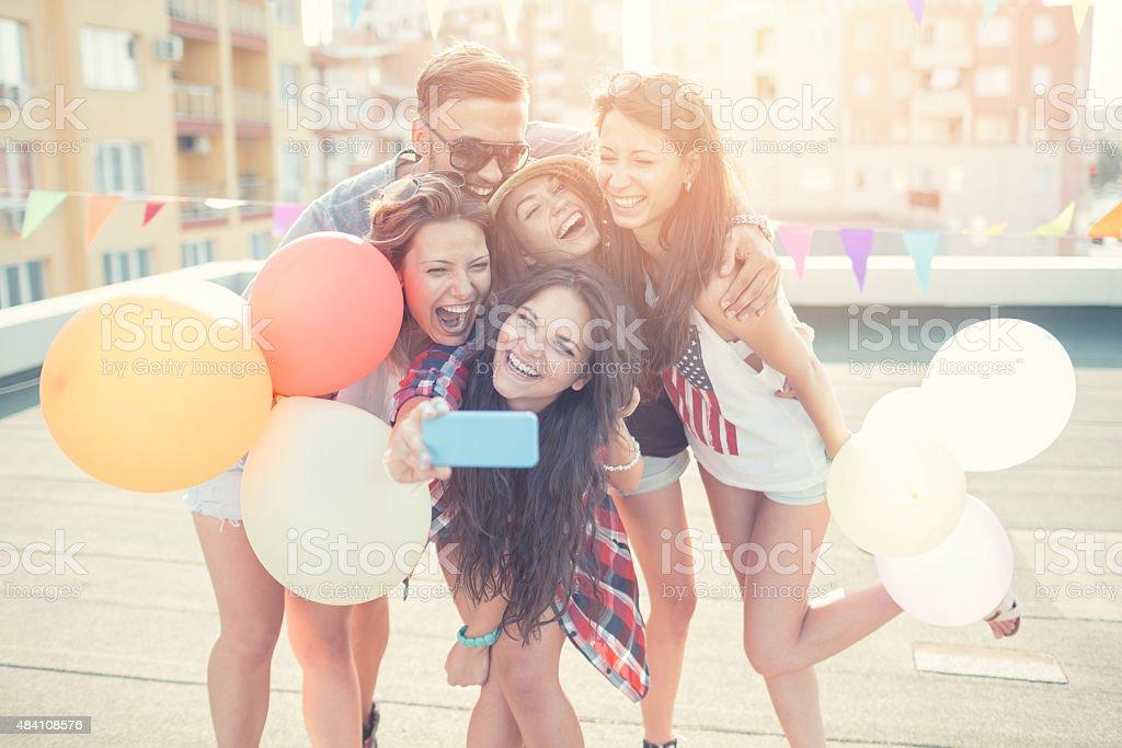 Amigos com balões e tirando selfie na cobertura - foto de acervo