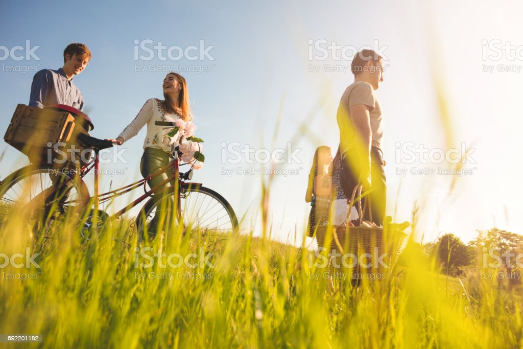 friends with bicycle and picnic box walking on pathway stock photo