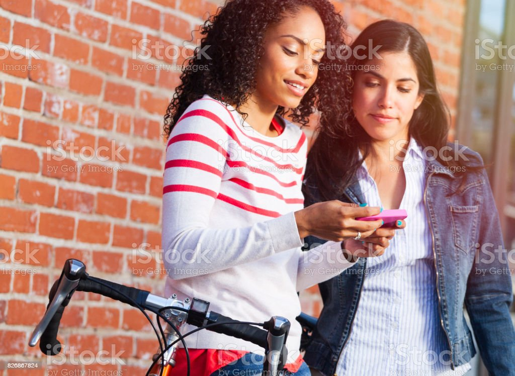 friends  with bike looking at smart phone stock photo