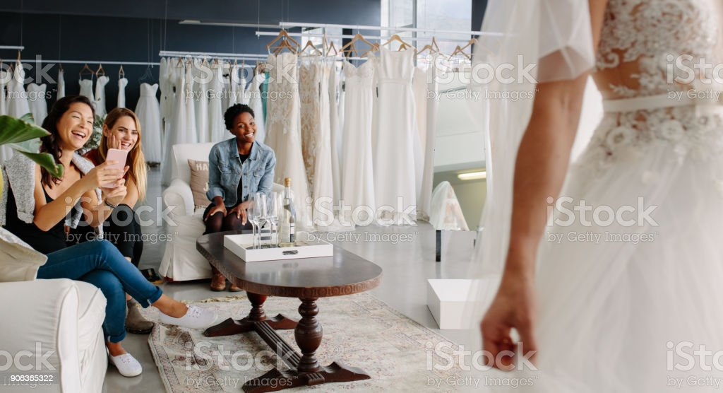 Friends with bride in bridal dress fitting room stock photo