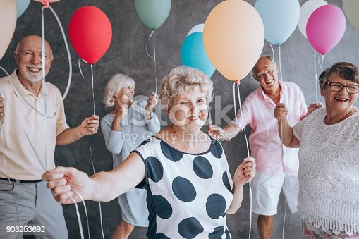 Smiling grandmother wearing blouse with black dots during New Year's Eve party with friends holding colorful balloons
