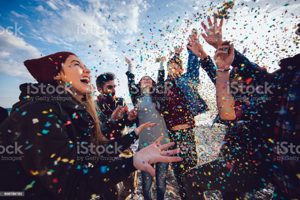 Friends with confetti partying and celebrating at the beach stock photo