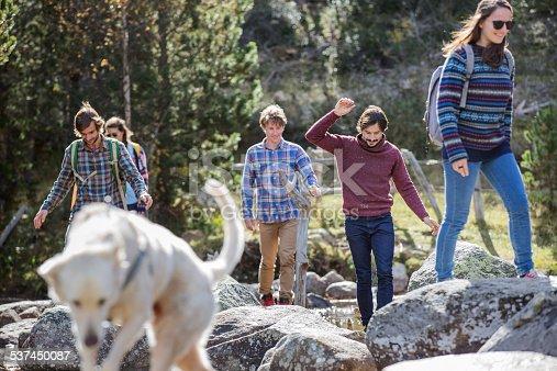 istock Friends with dog walking on rocks 537450087