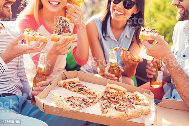 4 Friends With Drinks Sharing A Pizza Stock Photo - Download Image Now