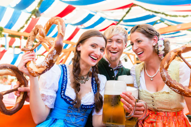 friends with giant pretzels in bavarian beer tent - german culture stock pictures, royalty-free photos & images