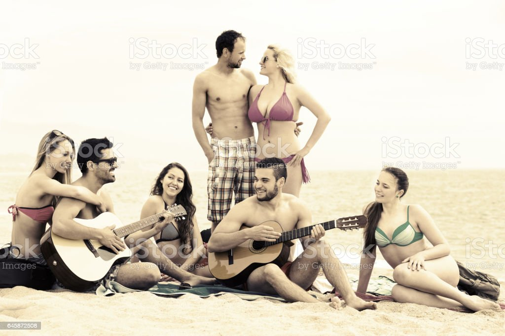 Friends with guitar at beach stock photo