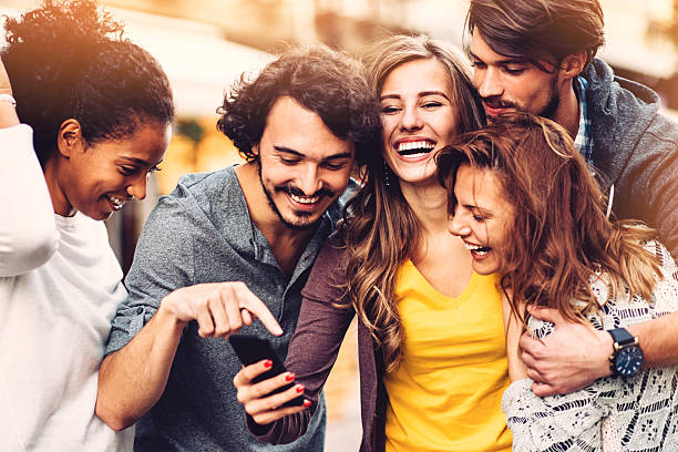 friends with phone outdoors - young adults hanging out stock pictures, royalty-free photos & images