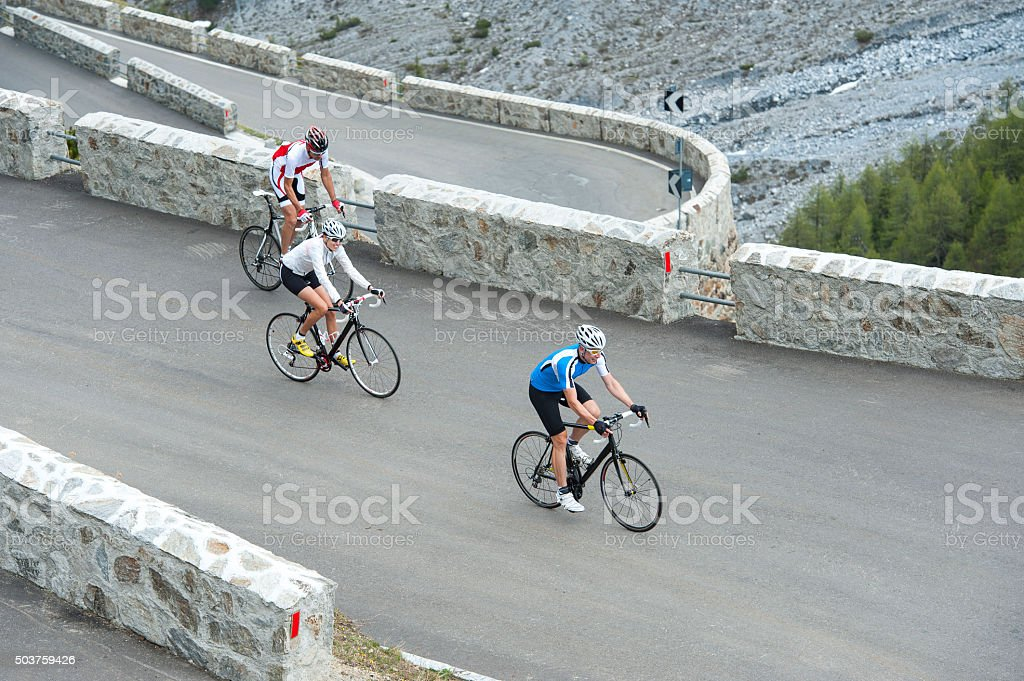 friends with road cycles on uphill stock photo