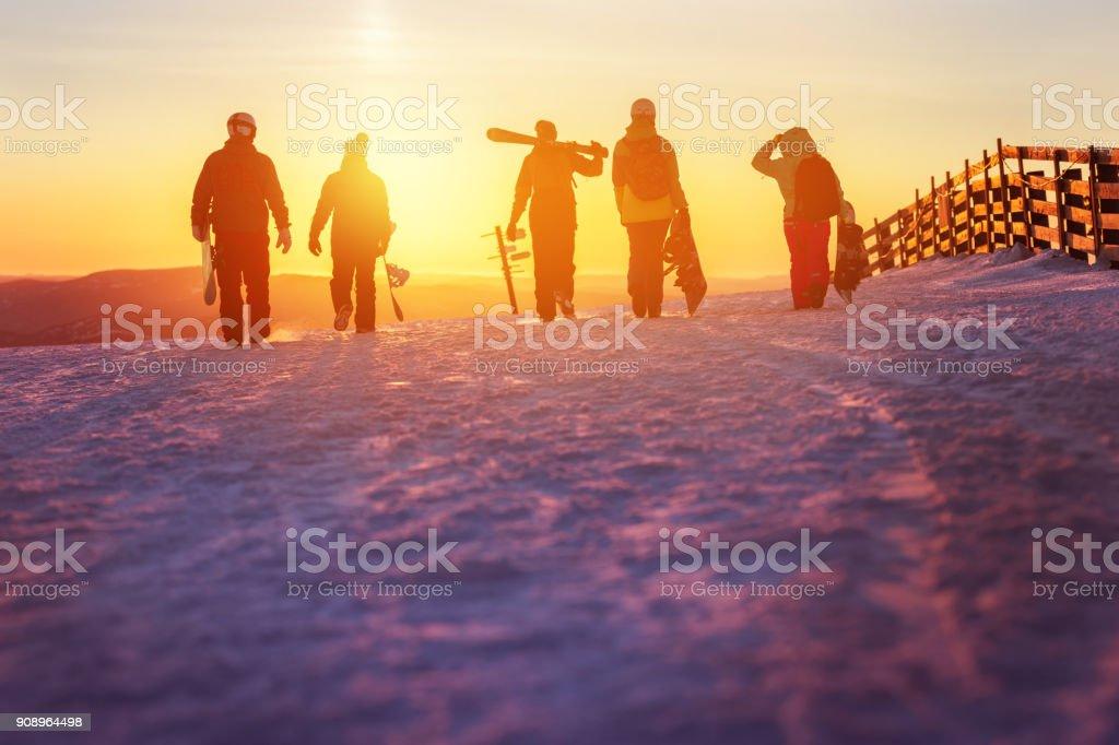 Amigos de esquí y snowboard a pie a la puesta del sol - foto de stock